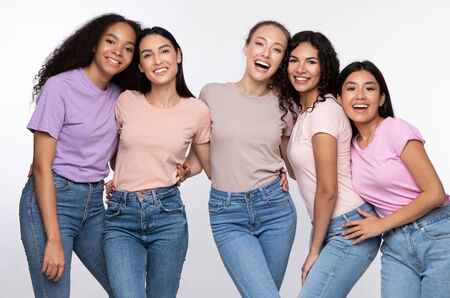 Five Happy Young Women Hugging Smiling To Camera Standing Over White Background. Female Unity Concept. Studio Shot 写真素材