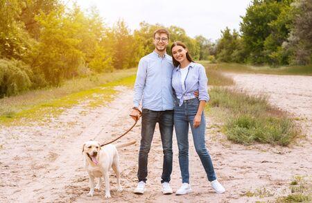 Concepto de retrato de familia. Novio y novia casuales paseando a su labrador retriever en el bosque, posando en la cámara