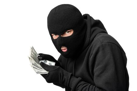 Greed Concept. Grumpy disguised criminal holding bunch of stollen dollars, isolated on white studio background Foto de archivo