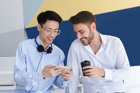 Male customer support operators with coffee and smartphone having break at call centre office