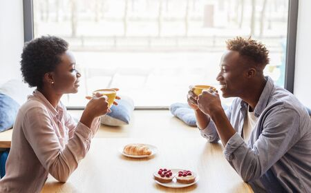 Side view of black boyfriend and girlfriend enjoying their coffee at cafe