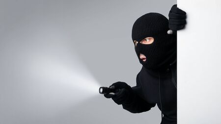 Disguised thief with robbery mask holding a flashlight behind a white panel isolated on gray studio background