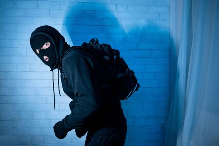 Burglary Concept. Sneaky and scared intruder wearing black balaclava hat lurking in the dark, looking at camera Stockfoto