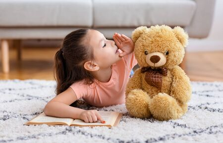 Kids Secrets. Little Asian Girl Reading Book Whispering Sharing Secret With Teddy Bear Playing Lying On Floor At Home.