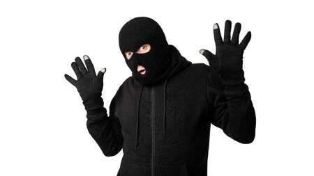 Hands Up. Masked looter being arrested by police, posing and standing isolated on white studio background