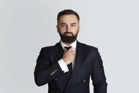 Serious businessman in office wear touching his necktie on grey background Foto de archivo - 149964797