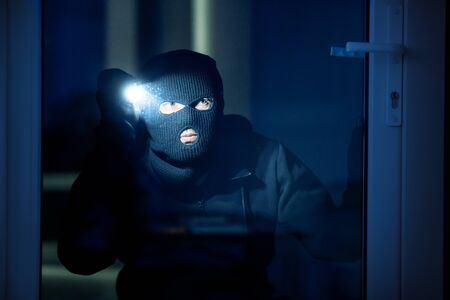 Spying Concept. Burglar in black balaclava hat watching whats inside the building in the night, using torch