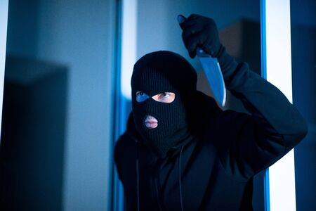 Crime Concept. Headshot of disguised criminal sneaking into apartment or office holding knife, ready to attack