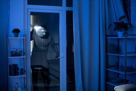 Criminal Act Concept. Masked robber looking at apartment through balcony door, using flashlight, copy space Stock Photo