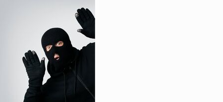 Scared thief in a balaclava and gloves raising hands up and looking out of blank sign with copyspace for your text