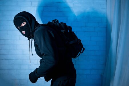 Marauding Concept. Stealthy criminal wearing black mask and hooded sweatshirt sneaking in house at night