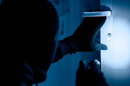 Vandalism Concept. Rear view of disguised burglar entering enclosed property, holding flash light, looking at lock Stockfoto