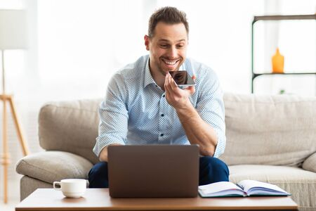 Happy Casual Businessman Using Voice Assistant On Smartphone, Looking At Laptop At Home Office, Copy Space
