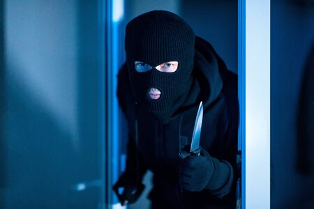 Homicide Concept. Murder in black balaclava hat breaking into house at night, holding knife in the dark, looking at you