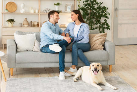 Domestic Atmospere Concept. Portrait of two people talking sitting on couch, labrador lying on the floor Imagens