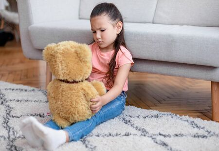 Kids Loneliness. Depressed Kid Girl Holding Teddy Bear Sitting Alone At Home. Copy Space