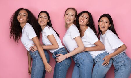 Five Multiracial Women Hugging Posing On Pink Studio Background, Smiling To Camera. Female Friendship Concept