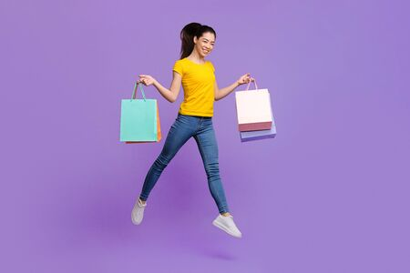 Happy Shopping. Joyful Asian Girl Carrying Lots Of Bright Shopper Bags And Jumping In Air Over Purple Background, Copy Space