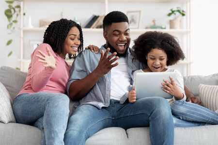Cheerful African Family Having Fun With Digital Tablet At Home, Watching Funny Videos And Laughing Together, Sitting On Couch In Living Room