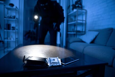 Burglary Concept. Robber breaking into residential building, using flash light on cash and smart phone lying on the table Stockfoto