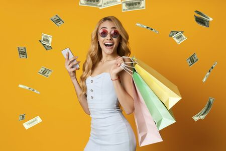 Cashback Concept. Creative Collage Of Woman With Smartphone And Shopping Bags With Falling Dollar Banknotes On Yellow Background