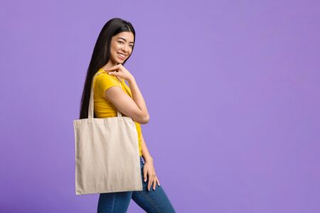 Eco Fashion. Cheerful Asian Girl Holding White Canvas Tote Bag And Posing Over Purple Studio Background, Copy Space Archivio Fotografico