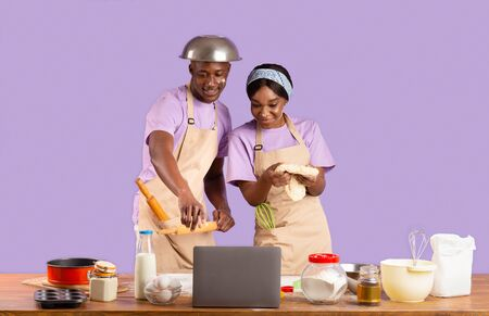 African American couple watching online culinary video on laptop while baking, violet background