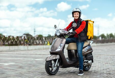 Food Delivery. Courier Guy Delivering Restaurant Meals In Box, Posing On Motorbike Outdoors. Empty Space For Text