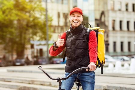 Food Delivery Service. Courier Gesturing Thumbs Up Standing With Delivering Backpack And Bike In City Outdoor. Free Space