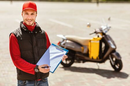 Courier Career. Delivery Man In Uniform Holding Folder Offering Delivering Services Standing Near Motorbike Outdoor. Copy Space