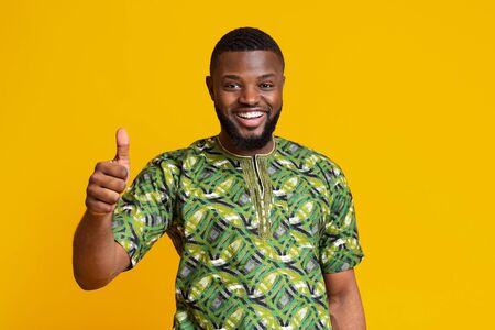 Black guy in traditional african costume showing thumbs up over yellow studio background
