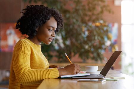 Young black lady taking notes in front of laptop, looking for job online at cafe, empty space
