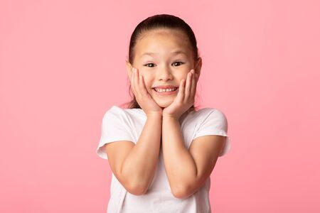 Wow. Closeup portrait of excited asian child touching her cheeks, isolated over pastel purple studio wall, copyspace