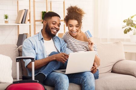 Planning Vacation Concept. Black Spouses Using Laptop And Credit Card Booking Tickets And Hotel Online Sitting On Sofa At Home.