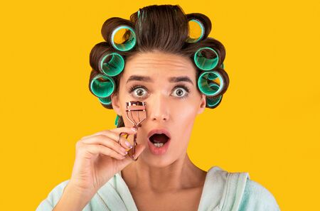 Shocked Housewife Holding Eyelashes Curler Looking At Camera Posing Standing In Studio Over Yellow Background. Beauty And Makeup.
