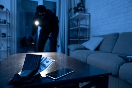Masked thief sneaking into apartment, using flashlight, selective focus on smartphone and wallet with money lying on table