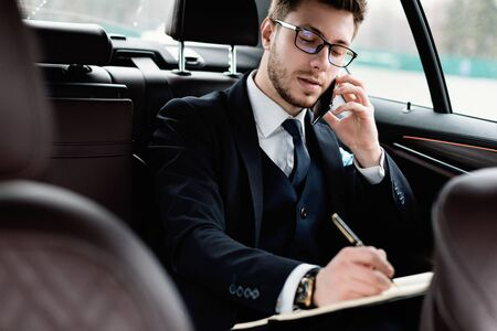 Always In Touch Concept. Young manager in glasses writing in notebook talking on smart phone sitting in back seat of car