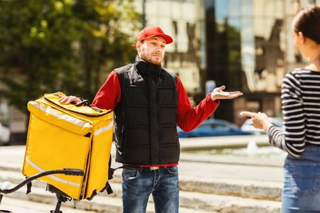Bad Delivery Service. Courier Delivering Customer Wrong Package Shrugging Shoulders Standing Outdoors. Selective Focus