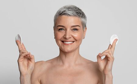 Skin Care Concept. Attractive Middle Aged Woman Posing With Cotton Pads In Hands, Smiling At Camera, Standing Over White Background, Panorama