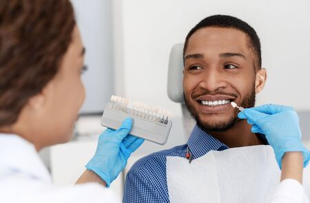 Female dentist choosing filling shade for smiling black guy, using tooth scale sample, close up Standard-Bild