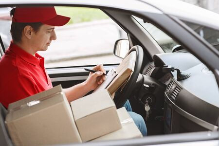 Modern express delivery service. Courier notes on tablet delivery of package sitting in car