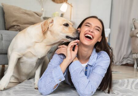 Togetherness Concept. Portrait of dog sniffing owners face, laughing girl lying on the floor at home