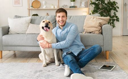 Youre My Best Friend. Portrait of handsome guy embracing his dog sitting on the floor in modern apartment