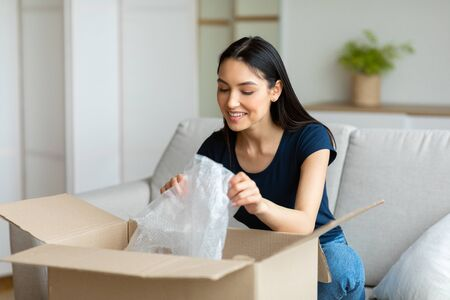 Delivery Service Concept. Cheerful Customer Girl Unpacking Box Smiling Sitting On Couch At Home