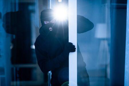Burglary Concept. Scared thief wearing black mask peeking into house through window or glass door, using flashlight