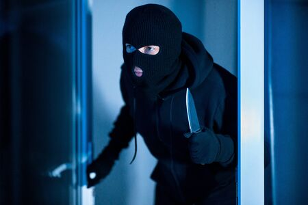 Masked criminal lurking in the dark, holding blade weapon, breaking into apartment through window or glass door