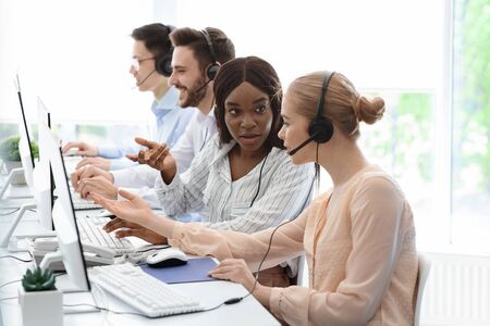 Female customer support workers solving clients problem together at call centre office