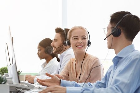 Call centre and customer service concept. Tech support operators discussing something at workplace