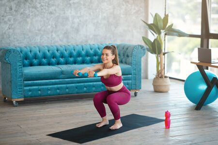 Strength workout at home. Lovely woman with dumbbells doing squat exercise in living room Foto de archivo