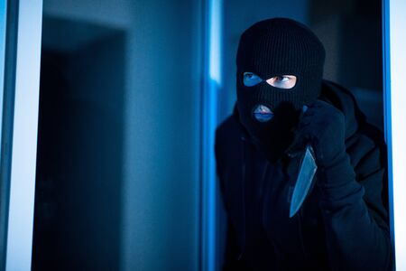 Violence Concept. Disguised prowler entering office through window or glass door with cold steel, searching for victim Stockfoto